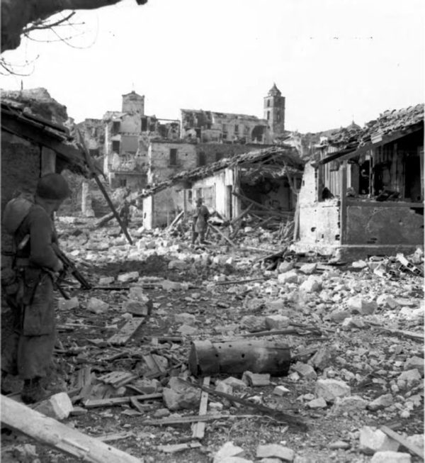 "<p>12 gennaio 1944. Verso le 11 del mattino le prime pattuglie del II battaglione del 168th Infantry Regiment entrano in Cervaro, appena evacuata dai tedeschi. Nella didascalia originale si afferma che <i>""Il sergente Charles Russell copre il sergente Barney Wight alla ricerca di cecchini. Due uomini di questa pattuglia furono uccisi poco dopo.""</i></p><p class='eng'>INFANTRY PATROL ENTERING CERVARO on 12 January 1944. The man atleft is carrying a tommy gun and covering the two men in front as they hunt for snipers. A few minutes after this picture was made two men of this patrol were killed by Germans hidden in the ruins. Cervaro is on the western slopes of the Rapido Valley. By this time the Fifth Army had fought its way through the Winter Line mountains. Fighting in this area had lasted from 15 November 1943 to 15 January 1944.</p>"