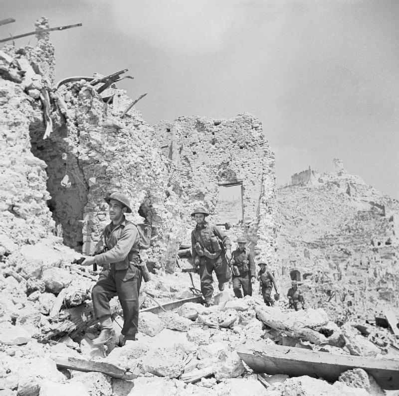 <p class='eng'>Men of the Durham Light Infantry advance through the ruins of Cassino, passing the remains of the Hotel Des Roses. Tanner (Capt). © IWM (NA14999)</p>
