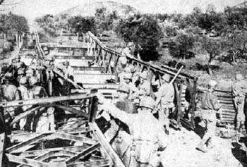<p class='eng'>A BAILEY BRIDGE ON HIGHWAY 6, near Mignano, is under construction by engineers of Company A, 235th Engineer Battalion. Possible bypasses through the olive trees on either side of the highway had to be cleared of mines (top). </p>